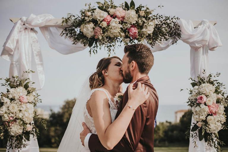 Baiser des mariés sous l'arche florale